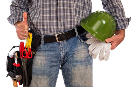 Adult craftsman carpenter isolated on white background making ok sign with thumb up, holding helmet and leather work gloves. Work tools industry construction, do it yourself housework. Stock photography.