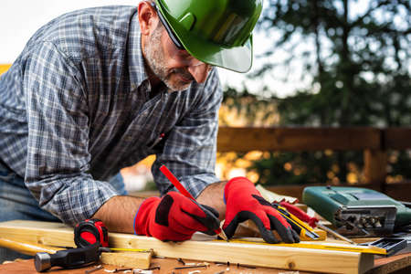 Adult carpenter craftsman wearing helmet and protective gloves, with a pencil and the carpenters square trace the cutting line on a wooden table. Construction industry, housework do it yourself. Stock photography.
