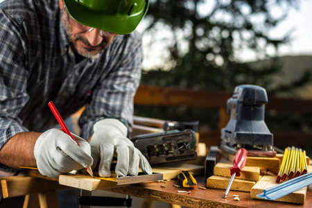 Adult carpenter craftsman wearing helmet and protective leather gloves, with a pencil and the carpenters square trace the cutting line on a wooden table. Construction industry, housework do it yourself. Stock photography.