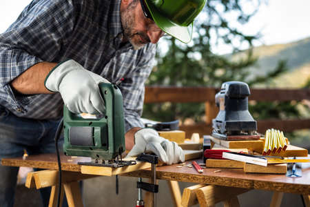 Adult carpenter craftsman wearing helmet and protective leather gloves, with electric saw working on cutting a wooden table. Construction industry, housework do it yourself. Stock photography.