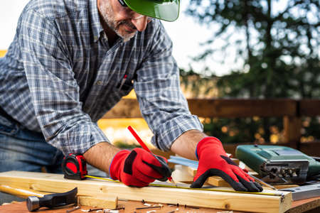 Adult carpenter craftsman wearing helmet and protective gloves, with the meter takes the measure on a wooden table. Construction industry, housework do it yourself. Stock photography.