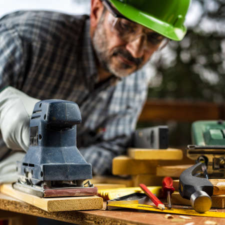 Adult carpenter craftsman wears protective leather gloves, with the electric sander smoothes a wooden table. Construction industry, housework do it yourself. Safety at work. Reklamní fotografie