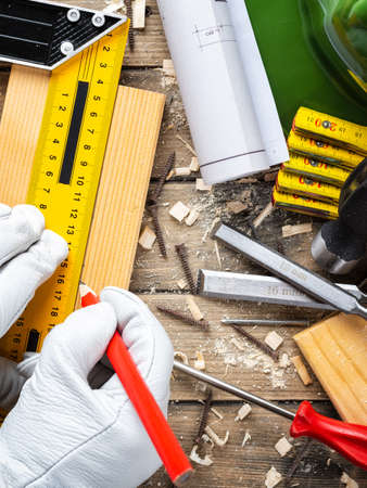View from above. Carpenter wears protective leather gloves, with the pencil and the carpenter's square draw the line on a wooden board. Construction industry, do it yourself. Wooden work table.