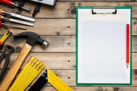 Draufsicht auf die Werkzeuge und das Notizbuch des Tischlers für Notizen auf einem antiken Holztisch. Baubranche, machen Sie es selbst. Arbeitstisch aus Holz. Standard-Bild