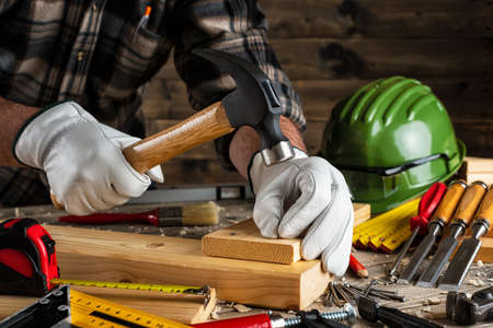 Close-up. Carpenter with his hands protected by gloves, with hammer and nails fixes a wooden board. Construction industry, do it yourself. Wooden work table.