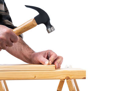 Close-up. Carpenter with hammer and nails fixes a wooden board. Construction industry, do it yourself. White background.