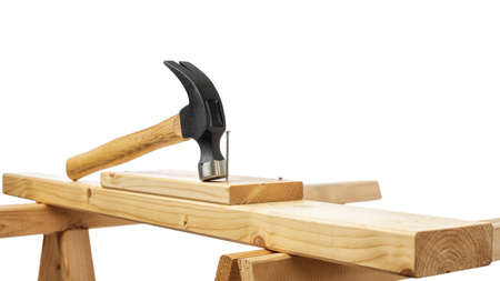 Close-up. Carpenter's hammer over a wooden board. Construction industry, do it yourself. White background.