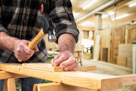 Close-up. Carpenter with hammer and nails fixes a wooden board. Construction industry, carpentry workshop.