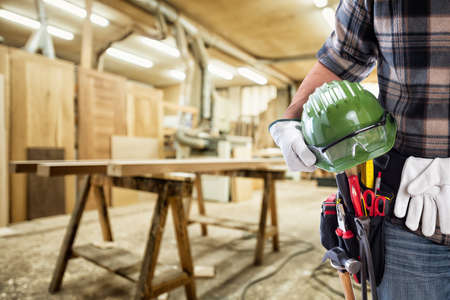 Close-up. Carpenter with hands protected by gloves holds helmet and protective goggles. Construction industry, carpentry workshop.