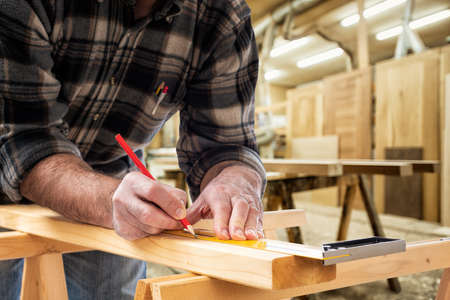 Close-up. Carpenter with pencil and carpenters square draw the cutting line on a wooden board. Construction industry, carpentry workshop.