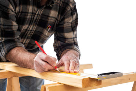 Close-up. Carpenter with pencil and carpenters square draw the cutting line on a wooden board. Construction industry. White background. Reklamní fotografie