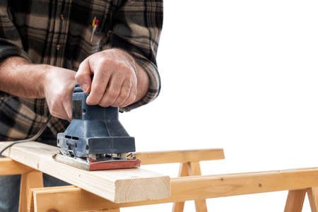 Close-up. Carpenter with the electric sander smoothes a wooden board. Construction industry. White background. Banque d'images - 138417368