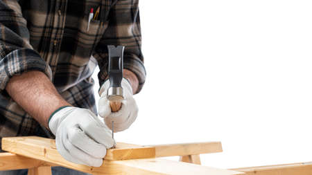 Close-up. Carpenter with his hands protected by gloves with hammer and nails fixes a wooden board. Construction industry. White background. Banco de Imagens