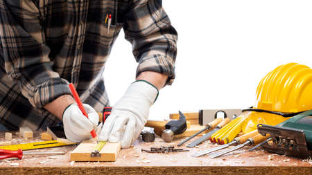 Close-up. Carpenter with his hands protected by gloves with a pencil and the meter marks the measurement on a wooden board. Construction industry. Isolated on a white background.