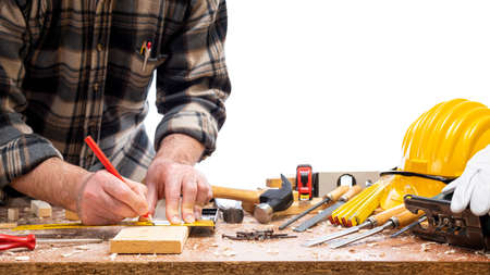 Close-up. Carpenter with pencil and carpenter's square draw the cutting line on a wooden board. Construction industry. Isolated on a white background. Standard-Bild