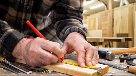 Close-up. Carpenter with pencil and the meter marks the measurement on a wooden board. Construction industry, carpentry workshop. 版權商用圖片 - 143805149