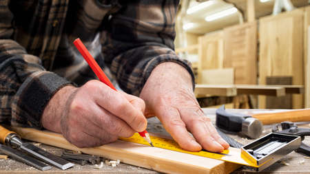 Close-up. Carpenter with pencil and carpenter's square draw the cutting line on a wooden board. Construction industry, carpentry workshop. 版權商用圖片 - 143805159