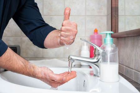Coronavirus prevention. Hand washing with hot soapy water stops the infection from Covid-19, OK sign with thumb up. Personal hygiene. Health.