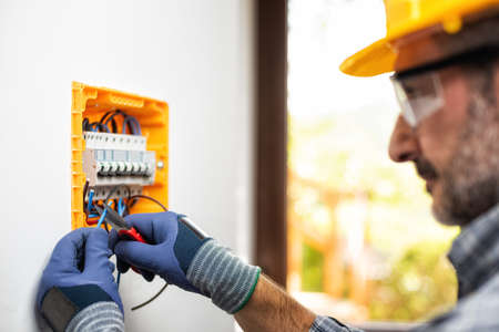 Electrician at work on an electrical panel protected by helmet, safety goggles and gloves; wear the surgical mask to prevent the spread of Coronavirus. Construction industry. Covid-19 Prevention. Stock Photo