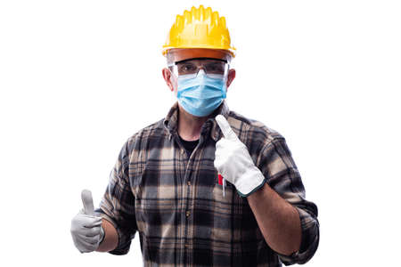 Carpenter worker isolated on white background wears surgical mask to prevent Coronavirus spread, makes OK sign with thumb up. Preventing Pandemic Covid-19 at the workplace.