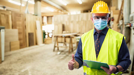 Engineer in carpentry workshop wears surgical mask to prevent Coronavirus spread, makes OK sign with thumb up. Preventing Pandemic Covid-19 at the workplace.