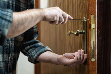 Close-up. Carpenter with screwdriver fixes the lock handle of a wooden door. Construction industry.