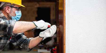 Carpenter worker at work repairs and installs a room door, wear the surgical mask to prevent Coronavirus infection. Preventing Pandemic Covid-19 at the workplace. Carpentry. Text space.