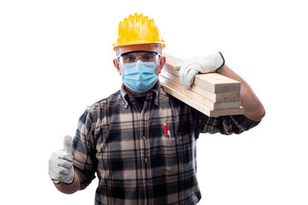 Carpenter worker isolated on white background wears surgical mask makes OK sign with thumb up.