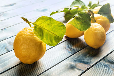 Closeup of ripe lemons with leaves on an old wooden table. Healthy nutrition. Health.