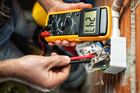 View from above. Electrician worker at work with the tester measures the voltage in a switch of a residential electrical system. Construction industry.