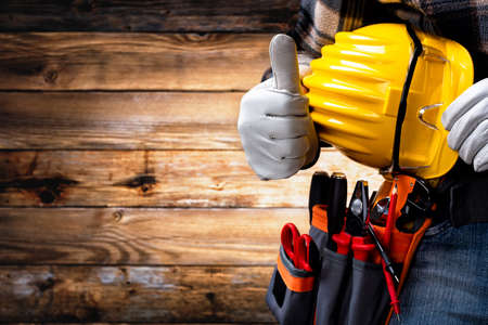 Electrician worker on vintage wooden background; wearing protective gloves and makes OK sign with his thumb up. Construction industry, electrical system.