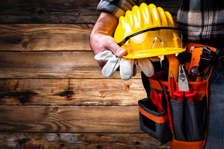 Electrician worker on vintage wooden background; holds helmet, gloves and goggles in hand. Construction industry, electrical system.