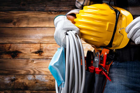 Electrician worker on vintage wooden background; holds the roll of electric cable, helmet, protective goggles and the surgical mask to prevent the spread of Coronavirus. Construction industry, work safety.