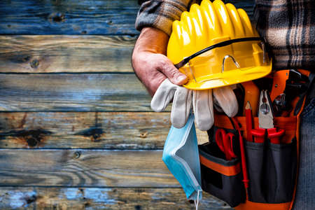 Electrician worker on vintage light blue wooden background; holds helmet, gloves, goggles and the surgical mask to prevent the spread of  virus. Construction industry, work safety. Standard-Bild