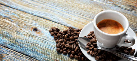 Top view. Beans and cup of hot Italian espresso coffee on a light blue rustic wooden background. Food and drink. Lifestyle.