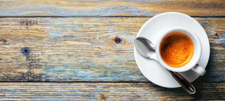 View from above. Cup of hot Italian espresso coffee on a light blue rustic wooden background. Food and drink. Lifestyle.