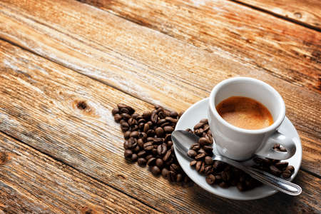 Top view. Beans and cup of hot Italian espresso coffee on a dark rustic wooden background. Food and drink. Lifestyle.