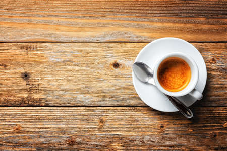 View from top. Cup of hot Italian espresso coffee on a dark rustic wooden background. Food and drink. Lifestyle.