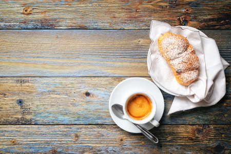 View from above. Cup of hot Italian espresso coffee and croissants on a light blue rustic wooden background. Food and drink. Lifestyle.
