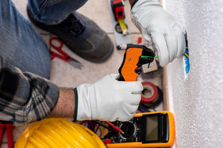 Top view. Electrician worker at work with wire stripper prepares the electrical cables of an electrical system. Working safely with protective gloves. Construction industry.