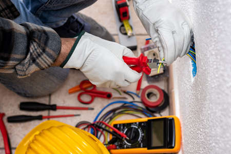 Top view. Electrician worker at work with cable cutter prepares the electrical cables of an electrical system. Working safely with protective gloves. Construction industry. Standard-Bild