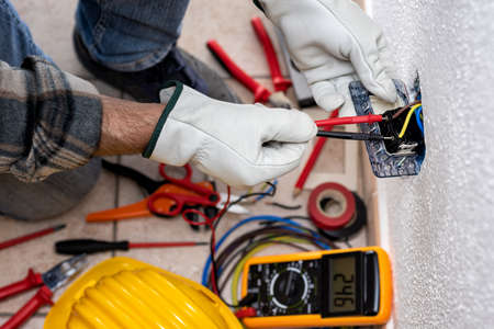 View from above. Electrician worker at work with the tester measures the voltage in an electrical system. Working safely with protective gloves. Construction industry.