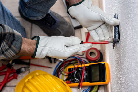 Top view. Electrician worker at work installs the electric socket of a residential electrical system. Working safely with protective gloves. Construction industry.