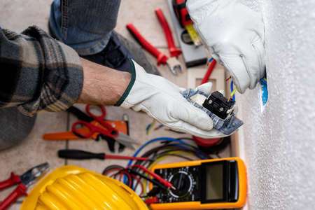 View from top. Electrician worker inserts electrical cables into the socket terminals of an electrical system. Working safely with protective gloves. Construction industry.