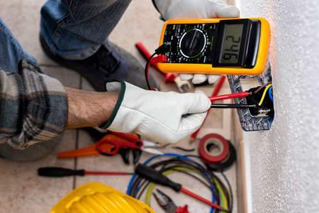 View from above. Electrician worker at work with the tester measures the voltage in an electrical system. Working safely with protective gloves. Construction industry. Foto de archivo