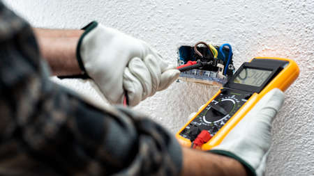 Electrician worker at work with the tester measures the voltage in an electrical system. Working safely with protective gloves. Construction industry. Standard-Bild
