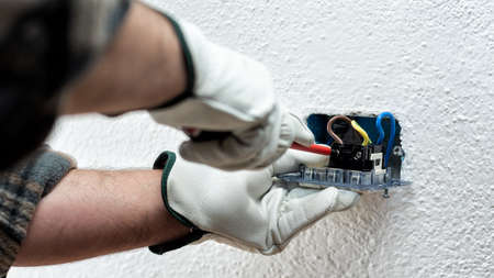 Electrician worker with screwdriver fixes electrical cables in the terminals of the socket of an electrical system. Working safely with protective gloves. Construction industry.