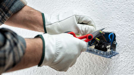 Electrician worker at work with scissors prepares the electrical cables of an electrical system. Working safely with protective gloves. Construction industry. Standard-Bild
