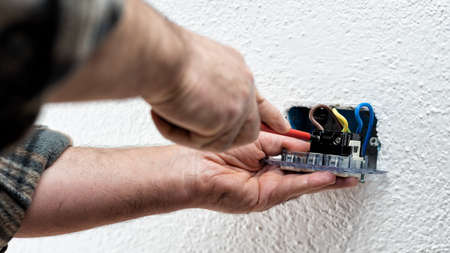 Electrician worker with screwdriver fixes electrical cables in the terminals of the socket of an electrical system. Construction industry. Standard-Bild