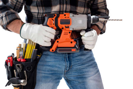 Carpenter worker at work holding rechargeable hammer drill, isolated on white background. Construction industry. Carpentry.